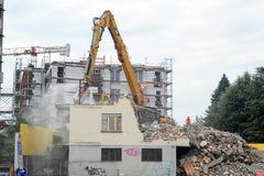 Construction workers during demolition of a house with a crane Stock Photos