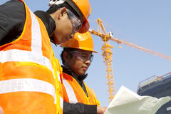 Construction workers with crane in background Royalty Free Stock Photo