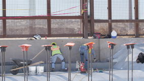 Construction Workers Doing Concrete Work Near Border. Construction workers doing concrete finishing near the border fence stock video footage