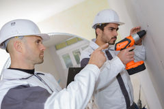 Construction workers drilling concrete wall Royalty Free Stock Images