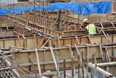 Construction workers fabricate ground beam formwork Stock Photos