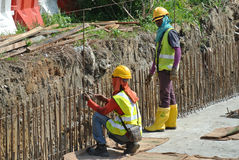 Construction workers fabricate retaining wall reinforcement bar at the construction site. Stock Images