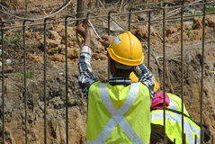 Construction workers fabricate retaining wall reinforcement bar at the construction site. Stock Photo