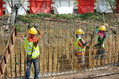 Construction workers fabricate retaining wall reinforcement bar at the construction site. Royalty Free Stock Image