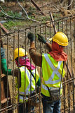 Construction workers fabricate retaining wall reinforcement bar at the construction site. Royalty Free Stock Images
