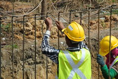 Construction workers fabricate retaining wall reinforcement bar at the construction site. Stock Photos