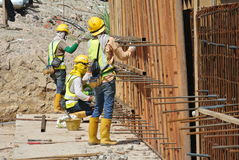 Construction workers fabricate retaining wall reinforcement bar and formwork at the construction site. Royalty Free Stock Photo