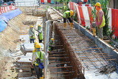Construction workers fabricate retaining wall reinforcement bar and formwork at the construction site. Stock Images