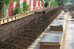 Construction workers fabricate retaining wall reinforcement bar and formwork at the construction site. Stock Photos