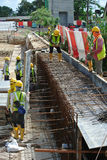 Construction workers fabricate retaining wall reinforcement bar and formwork at the construction site. Royalty Free Stock Image