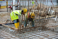 Construction workers fabricate steel reinforcement for concrete wall at the construction site. Stock Image