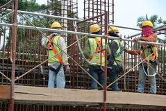 Construction workers fabricate steel reinforcement for concrete wall at the construction site. Stock Photo