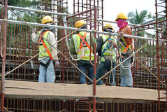 Construction workers fabricate steel reinforcement for concrete wall at the construction site. Stock Images