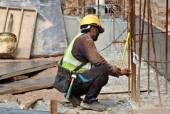 Construction workers fabricate steel reinforcement for concrete wall at the construction site. Stock Photography