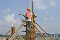 Construction workers fabricating column timber formwork Royalty Free Stock Image