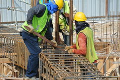 Construction workers fabricating ground beam reinforcement bar Stock Image