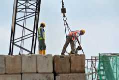 Construction workers hoisting load test block at the construction site. SELANGOR, MALAYSIA – MARCH 2015: Construction workers arranging load test block at the Royalty Free Stock Photo