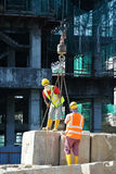 Construction workers hoisting load test block at the construction site. SELANGOR, MALAYSIA – MARCH 2015: Construction workers arranging load test block at the Stock Photos