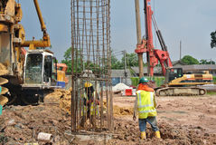 Construction workers install bore pile reinforcement bars Stock Image