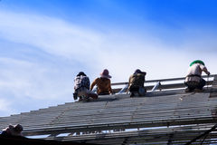 Construction workers install a steel roof. Stock Images