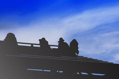 Construction workers install steel roof silhouette. Royalty Free Stock Image