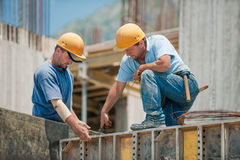 Construction workers installing formwork frames. Two authentic construction workers collaborating in the installation of concrete formwork frames Royalty Free Stock Image