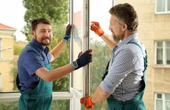 Construction workers installing new window. In house stock image