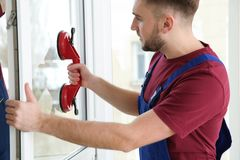 Construction workers installing plastic window. In house royalty free stock images