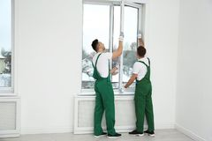 Construction workers installing plastic window. In house stock images