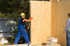 Construction workers installing prefab walls. Construction workers installing insulated wooden prefab walls in the corner of a new build home on a building site Stock Images