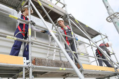 Construction workers installing scaffolding