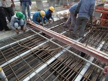 Construction workers are installing steel rods in reinforced concrete post tension site concrete steel. Construction workers are installing steel rods in royalty free stock image