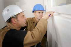Construction workers installing window in house. Apprentice royalty free stock photography