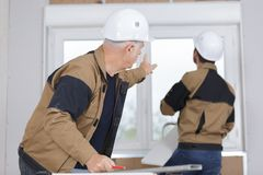 Construction workers installing window in house. Fitting royalty free stock photos
