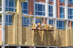 Construction workers insulating house facade. External wall insulation system or EWIS mineral wool for energy saving. Construction workers insulating house stock photography
