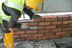 Construction workers laying bricks at construction site Stock Images