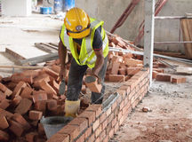 Construction workers laying bricks at construction site Stock Image