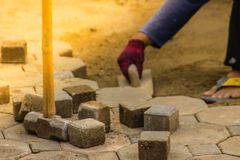 Construction workers are laying concrete pavement stone for footpath work at the construction site. Paving stone worker is putting. Down concrete pavement stock photo