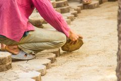 Construction workers are laying concrete pavement stone for footpath work at the construction site. Paving stone worker is putting. Down concrete pavement royalty free stock photo