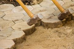 Construction workers are laying concrete pavement stone for footpath work at the construction site. Paving stone worker is putting. Down concrete pavement royalty free stock image