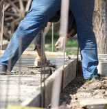 Construction workers leveling concrete pavement. Royalty Free Stock Photos