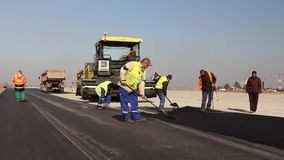Construction workers leveling fresh asphalt pavement