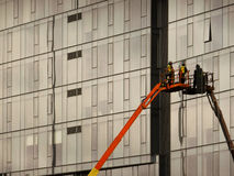 Construction Workers on a Lift. Two construction workers on a lift working on a mirrored building Royalty Free Stock Images