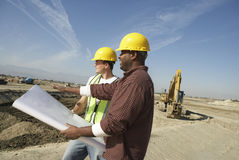 Construction Workers Looking At Plan On Site Royalty Free Stock Photos