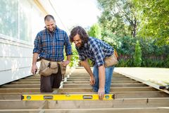 Construction Workers Looking At Spirit Level On Royalty Free Stock Photos