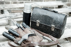 Construction Workers Lunch Break. With lunch pail, beverage container, tool belt, hammer, screwdrivers, and wrenches on wooden pallet with brick wall in royalty free stock images