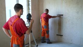 Construction workers make measurements with laser tool on building site. Male workers control red beam level accuracy on concrete wall. Safety policy stock footage