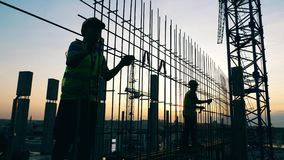 Construction workers are making a metal framework at sunset. 4K stock footage