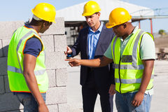 Construction workers manager. Construction workers with their manager checking bricks quality Royalty Free Stock Photo