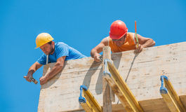Construction workers nailing formwork in place. Authentic construction builders working together for nailing wooden cement formwork in place Stock Photography